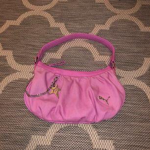 Riktigt häftig Y2K väska i rosa från Puma! Köpt på myrornas, säljs då den aldrig kommer till användning! Jätte trendig och väldig vintage (90/00)! Unik och i superfint skick! Kedja och detalj är i silver