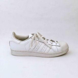 Klassiska sneakers från Adidas, modell Superstar. Begagnade med några skråmor och smutsfläckar på in -och utsidan. Annars i bra skick. Material: Skinn med mjukt textilfoder. Storlek: UK 6. Fraktkostnad tillkommer.
