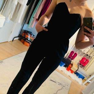 En svart jumpsuit från H&M i storlek 32, är uppsydd så passar mig i längden som är 160cm! Har fickor & dragkedja på sidan. Jag kan frakta om köparen står för frakten & jag har swish, mer bilder kan skickas!💌
