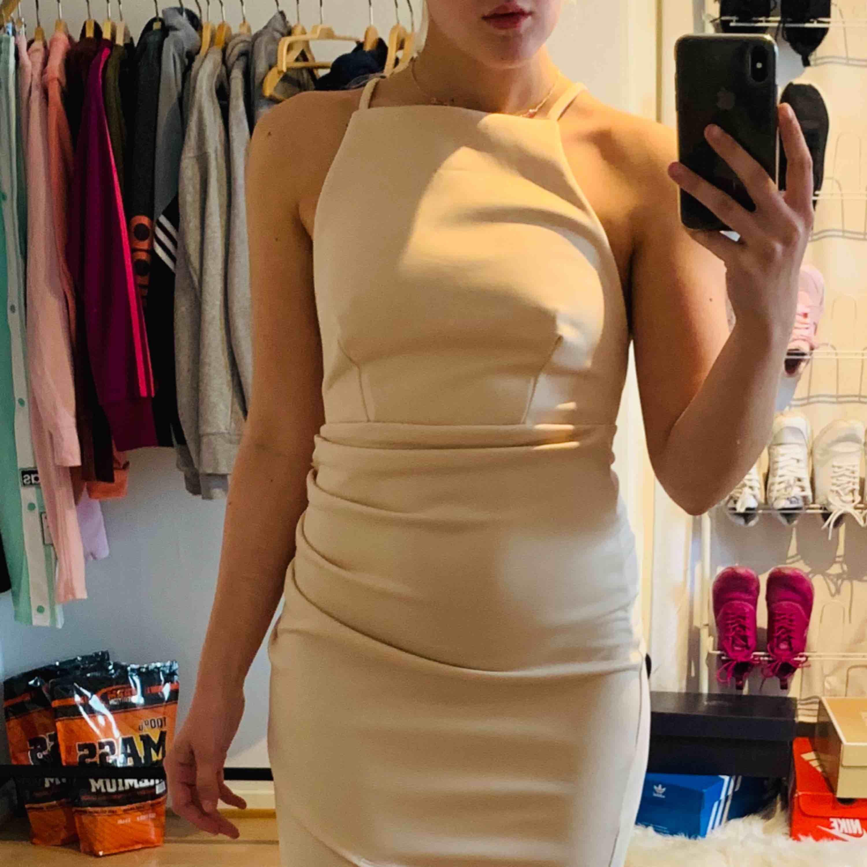 Beige klänning från Nelly med öppen rygg i storlek S, fint skick! Jag kan frakta om köparen står för frakten & jag har swish, mer bilder kan skickas!💌. Klänningar.