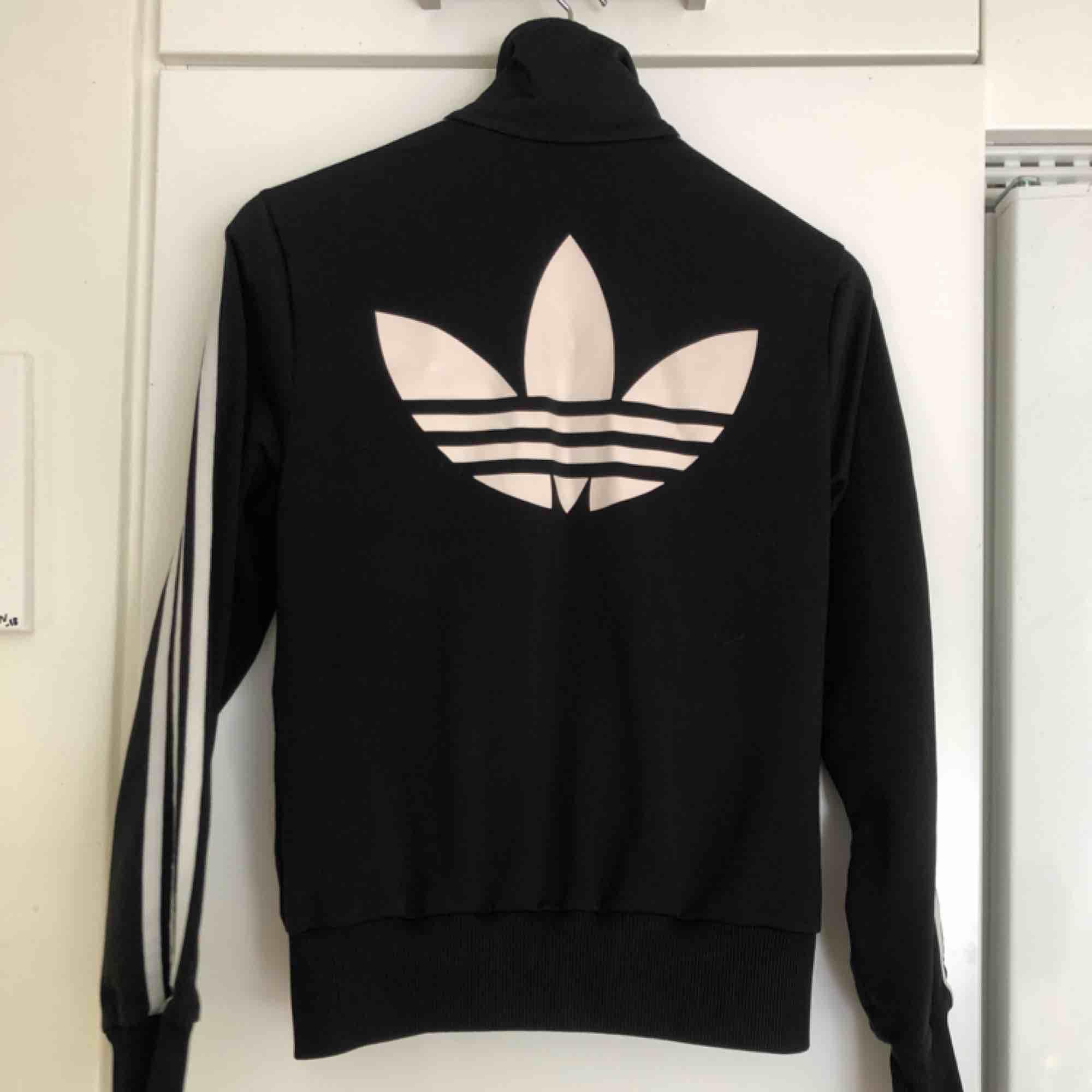 Svart Adidas zip-tröja i wct-material, vit stor logga på ryggen och mindre logga på ena bröstet .. Jackor.