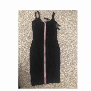 En svart klänning som är både stretchig och tajt i modellen. Klänningen har en dragkedja på framsidan som är en väldigt fin detalj! Klänningen är oanvänd då den är för liten för mig i bysten men längden är perfekt då jag är 162 cm!