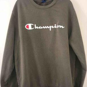 En militärgrön Champion sweatshirt i storlek XL, färgen syn inte så bra på bild så se bild 3 för den riktigare färgen (en annan sweatshirt, bild tagen från internet) knappt använd, jätte bra skick!