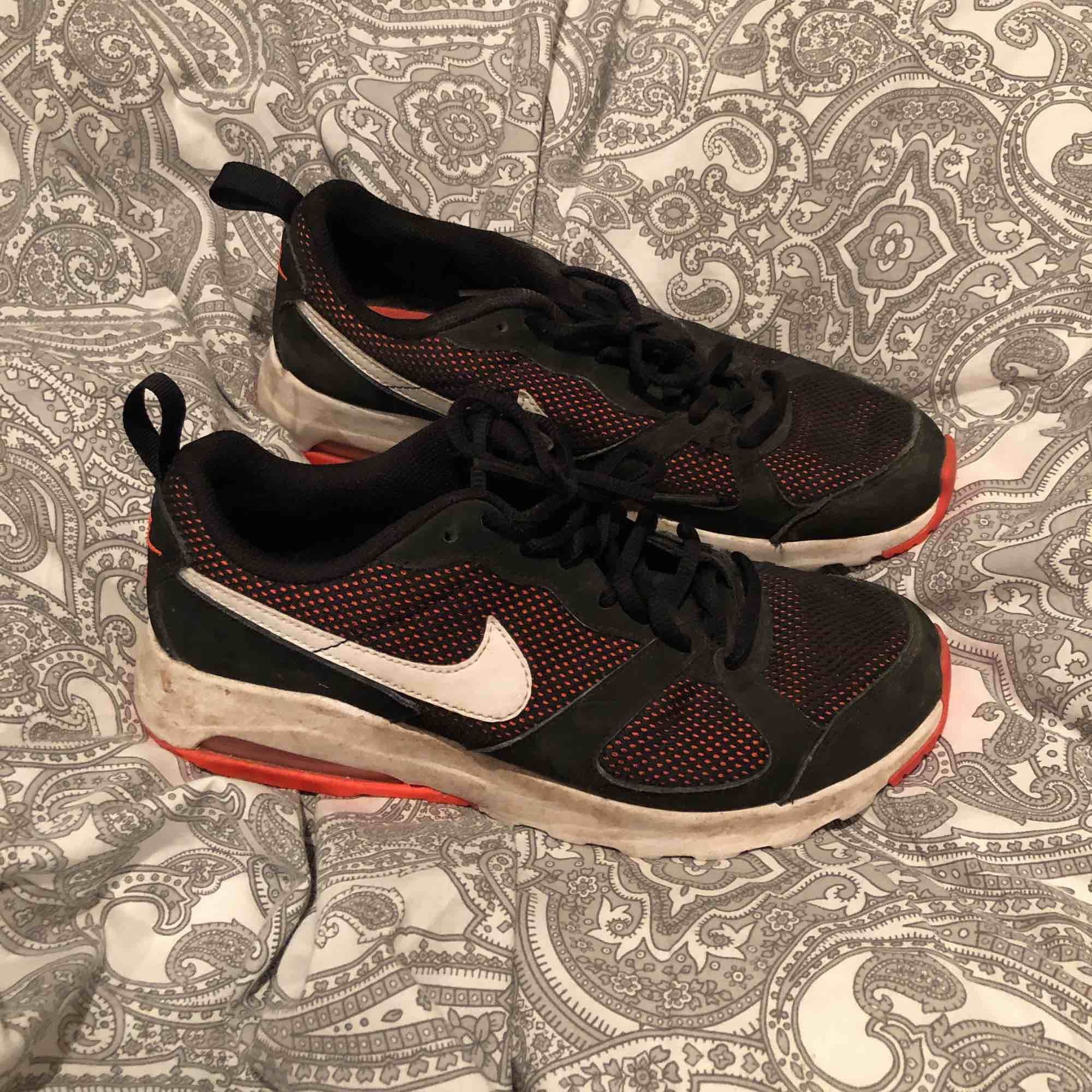 Svarta Nike gympaskor med orange detaljer. Storlek 40. Skor.