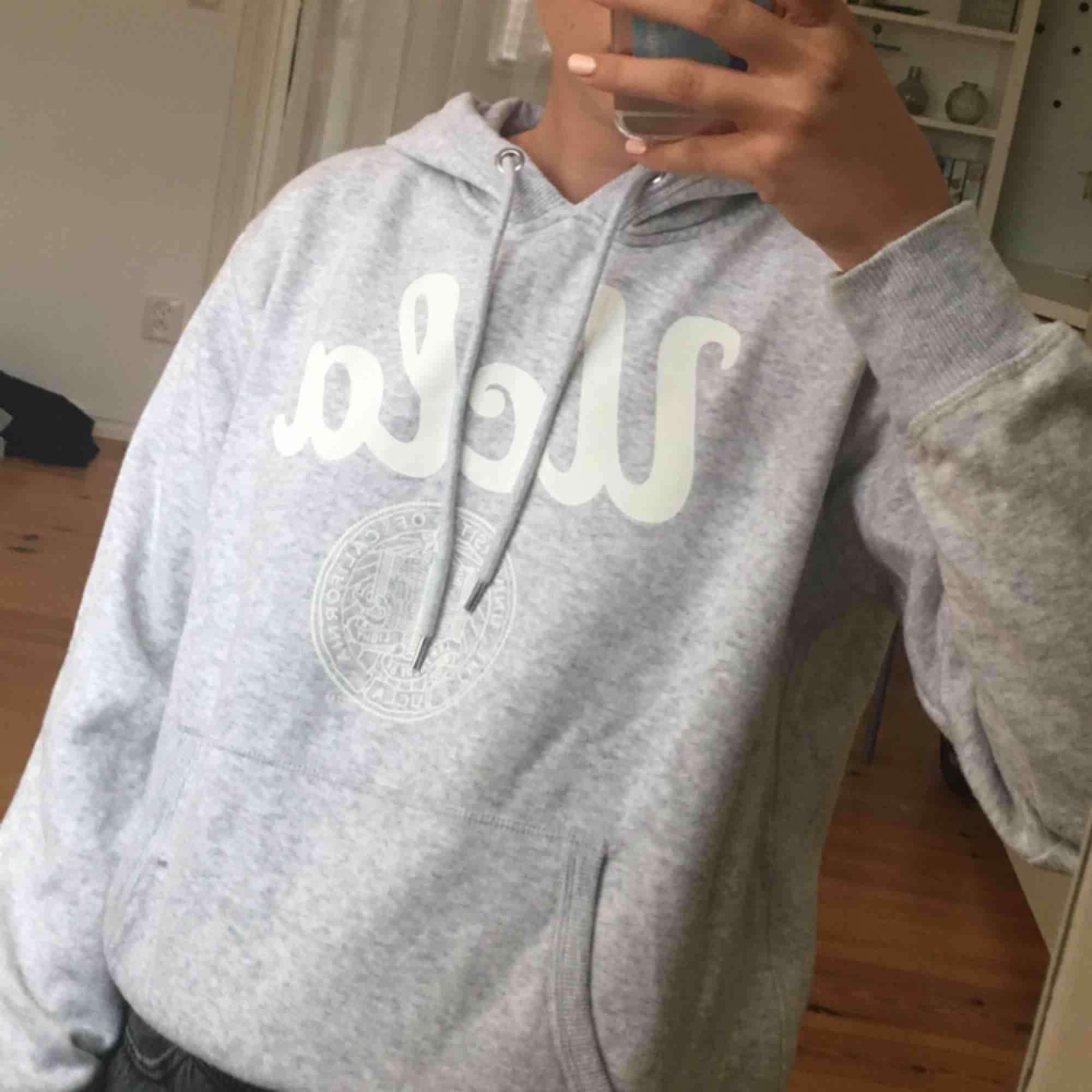 En ljusgrå hoodie (med luva, syns inte bra på bilderna) med vitt tryck. Kommer ifrån H&M. Knappt använd och i väldigt fint skick!  Även mjuk inuti. OBS! Notera att totalpriset är 104kr då frakten är 54kr.. Huvtröjor & Träningströjor.