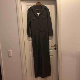 Grå långärmad jumpsuit från ZARA ifrån trf collection. Storlek S helt oanvänd med prislappen kvar. Köpt för 549 och säljs pga felköp.