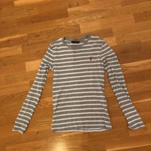 Grå vit randig Ralph lauren långärmad tröja.  Storlek S och använd mycket. Säljes billigt pga ett litet hål vid armhålan.