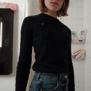 En långärmad stickad tröja från Gant i en      mörkblå färg. Tröjan är mycket strechig men samtidigt sitter den