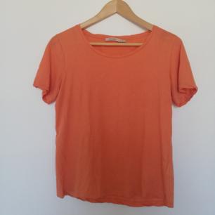 Orange t-shirt i modell Vanya från Whyred. Sparsamt använd men har tyvärr kommit ett minimalt hål längst ner på framsidan, säg till så skickar jag bild. Frakt 42 kr.