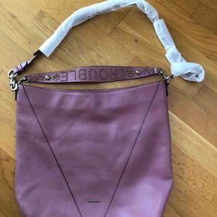 ÄktaRebecca Minkoff stor tote väska Ny. Fått lite avtryck legat i garderoben med nåt tungt över. Fyller man väskan så syns det knappt el så bär du den på andra sidan  bär väskan på axeln med både den kortare axelrämmen el den långa Färg lila skinn