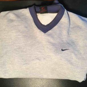 En mysig grå Nike sweater med blå rand på ärmarna och v-hals. OBS! På sista bilden ser man två små vid halsen, men inget man tänker på eller syns tydligt.