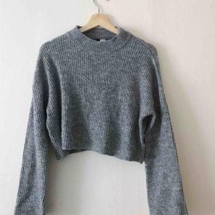 Grå midjekort stickad tröja. Med halvpolo och vid ärm. Perfekta tröjan till höga byxor. Mjuk och varm till hösten 🍂