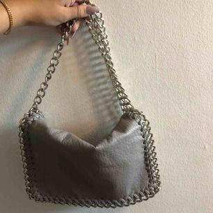 Beige/grå väska från tiamo med axelband, använd fåtal gånger så är i fint skick, frakt 90kr
