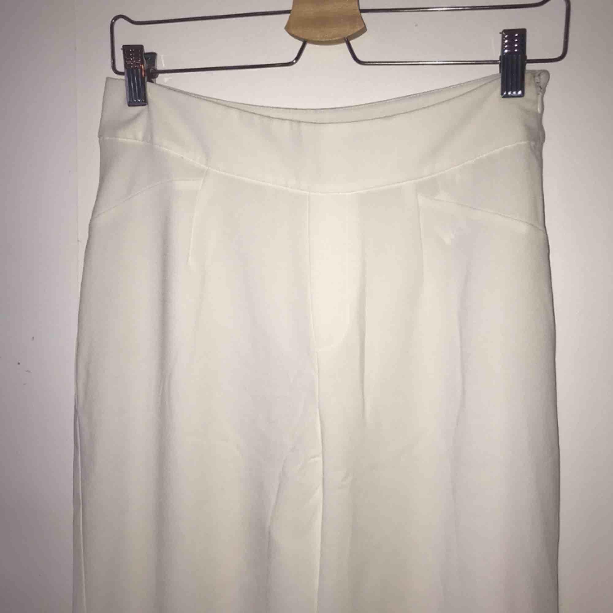 Vita kostymbyxor i något kortare modell och silkigt material. Köpta på Bershka. Storlek 38 . Jeans & Byxor.