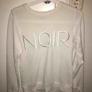Vit tröja med texten NOIR