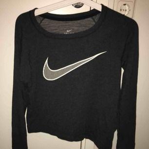 Grå Nike sweater som är snett croppad nertill