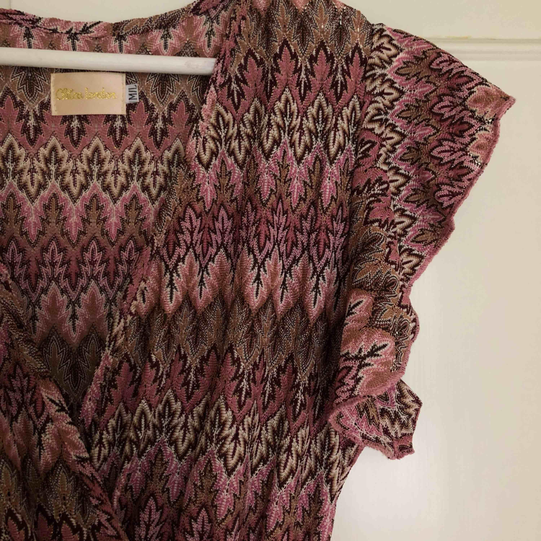 Mönstrad v-ringad klänning med markerad midja, lång bak kortare fram. Lila, beige och lite glittertrådar. Använd vid ett tillfälle. Nypris 699 kr. Hel, ren och som ny!. Klänningar.