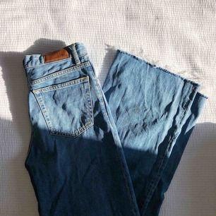 Jeans med hög midja, knappknäppning i gylfen och rå kant. Använda ett par gånger, därefter tvättade en gång. Vida och ankellånga ben.