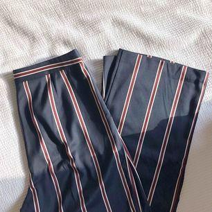 Randiga kostymbyxor med hög midja och glansigt material. Rejäla med innerfoder. Nypris 550 kr, från ASOS.