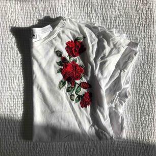Vit t-shirt med broderade rosdetaljer. Fri frakt!