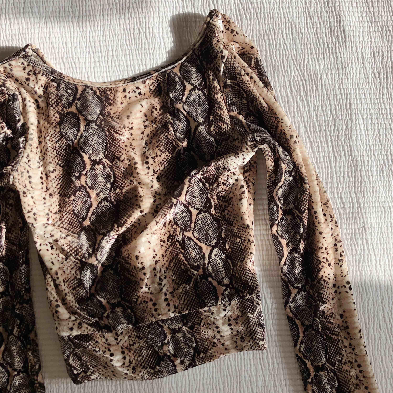 Långärmad croptop i snakeprint och v-ringad rygg. Tight passform och mjukt sammetsliknande material. Använd vid ett tillfälle.. Toppar.