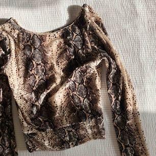 Långärmad croptop i snakeprint och v-ringad rygg. Tight passform och mjukt sammetsliknande material. Använd vid ett tillfälle. Fri frakt!