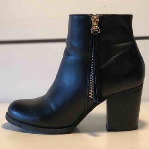 Ett par svarta bootsklackar med kedjedetalj. En av skorna har ett litet märke på sidan (bild 3), klackarna är något nötta (från normal användning) och det finns några små märken på skorna. Detta är dock inte något man tänker på när man bär dem.