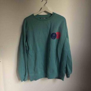 Turkos sweatshirt med två emojis. Mysig inuti och jättefin till svarta jeans. Oanvänd. Varm till hösten. Passar S/M och är fint oversized.