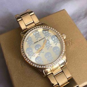 Oanvänd Mark Maddox Gold Dial Gold-plated stainless steel klocka Modell # MM0002-97  Originalpris: ca 750 kr  Tål 30 meters vattendjup Mer produktinfo finns här:  http://www.bodying.my/mark-maddox-watches-mm0002-97/watches/137219#.XU2XDRaezDs