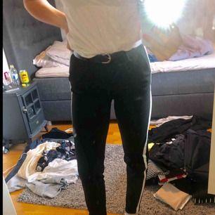 Svarta kostymbyxor med vita ränder efter benen, bra skick (knappt använda) & väldigt sköna.  Betalning sker via swish.