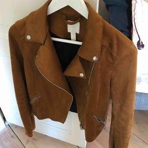 Snygg bikerjacka i äkta mocka från H&M premium i höstig färg. Silverdetaljer. Använd ca 2 gånger då den tyvärr är i fel storlek för mig. Köpt för 999kr.