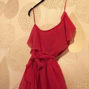 Rosa klänning som går ungefär till knäna Ena axeln är bar och klänningen knyts med snöre i midjan