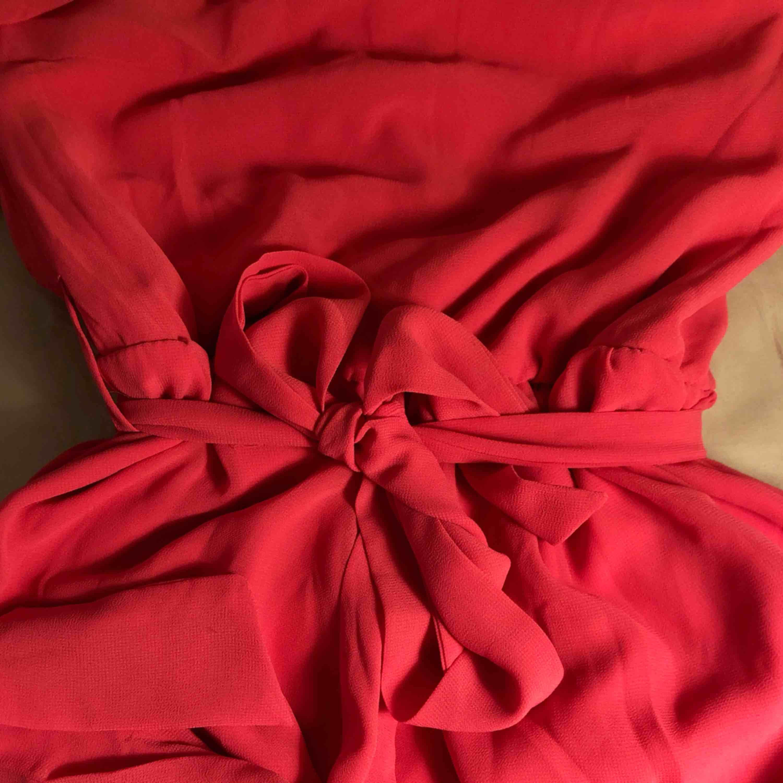 Rosa klänning som går ungefär till knäna Ena axeln är bar och klänningen knyts med snöre i midjan. Klänningar.