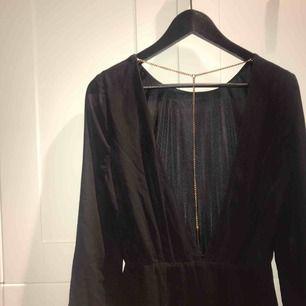 Svart klänning med öppen rygg och gulddetaljer från Bikbok i stl. S, 100 % polyester. Bra skick!