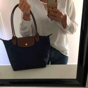 Säljer min mörkblåa klassiska longchamp väska som jag använt max 3 ggr!!! Det är den lilla modellen men trots det väldigt rymlig så en får plats med allt den behöver