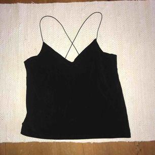 Svart linne med korsade band i ryggen, stl. M från Gina Tricot