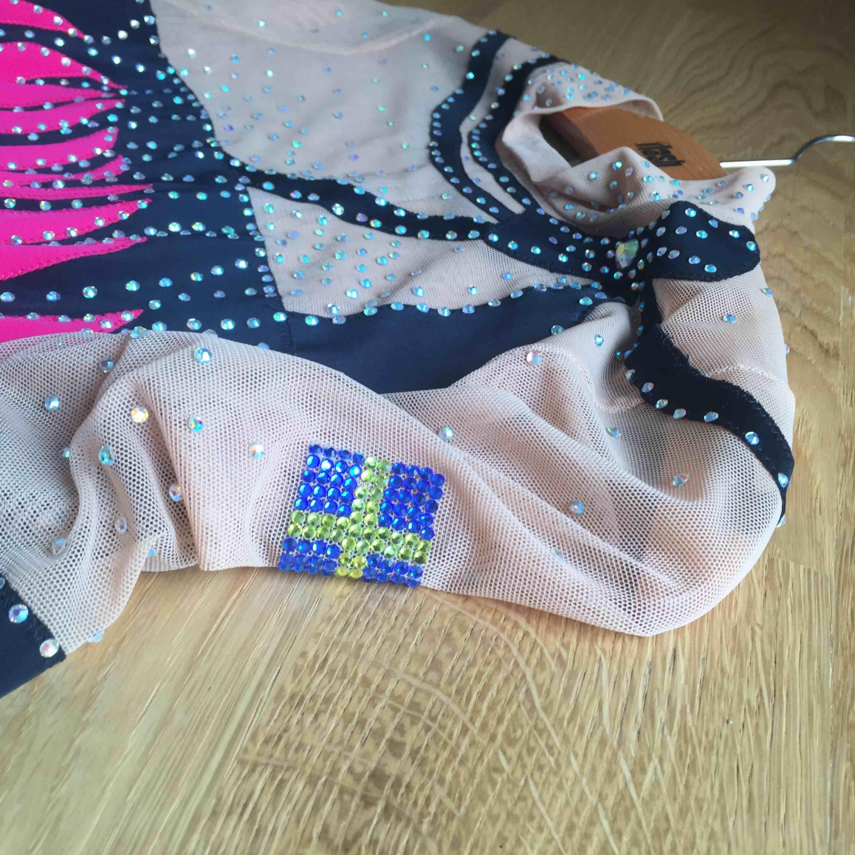 En rosa och svart rytmisk gymnastik dräkt i begagnat men fint skick. Har använts flera gånger, passar perfekt till tävlingar. Har burits på tävlingar på nationell nivå. Fint detaljerat med stenar, även Sveriges flagga på axeln. Hämtas i Kalmar. Klänningar.