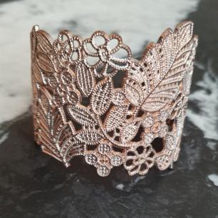 Hårt armband i guldaktig färg med små stenar
