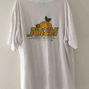 Vit T-shirt med tryck fram och bak, det större trycket är på baksidan. Köpt på weekday