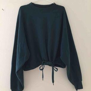 Mörkgrön/mörkturkos sweatshirt med knytning i midjan. Köpt på weekday för 350 kr