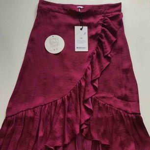 Satin wrap over kjol från NA-KD. Kjolen är endast testad och därmed som ny.  Material: Satin Färg: Lila/rosa/vinröd (Burgundy)  (frakt tillkommer)