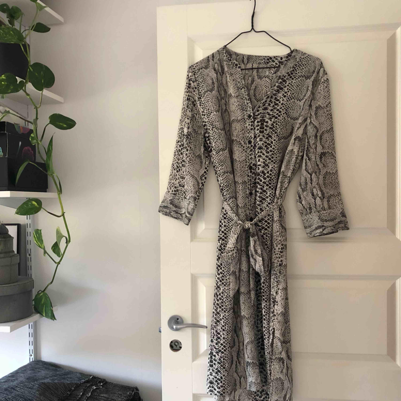 Ormmönstrad klänning eller tunika med knyte i midjan . Klänningar.
