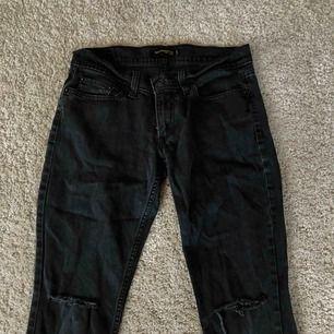 Lågmidjade jeans från Levi's med hål på knäna. Rätt så urtvättade men det finns folk som gillar lightwash-stilen. Står ingen storlek någonstans, men skulle gissa på något mindre än M.
