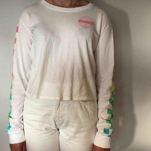 Vit långärmad Hollister tröja med färgglatt shackmönster på ärmarna och stort tryck på ryggen. Är en storlek S men är stor i storleken. Kan skickas emot fraktavgift.