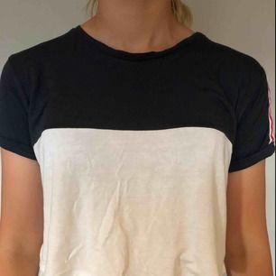 Blå och vit croppad T-shirt från pull&bear med rödvita revärer på axlarna.