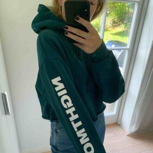 Avklippt mörkgrön hoodie med coolt tryck på båda armar och även på luvan. Frakt 54kr