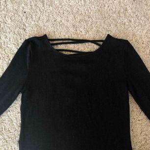 """Svart tröja med """"knytning"""" på ryggen eller vad man säger, väl använd. Vet inte riktigt vart den är ifrån men tror att jag köpte den på h&m."""
