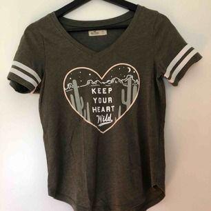 Mörkgrön T-shirt från Hollister med tryck! Den är använd ett fåtal gånger och i ett väldigt bra skick. Jag skulle säga att t-shirten är som en i storlek S!  Köparen står för frakten!