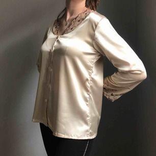 Så fin blank pyjamasskjorta i ljust guld med knappar framtill och spets i beige med mörkrött mönster vid krage och ärmar • perfekt till både vardags och fest • ingen storlek men sitter som en M • i bra skick!