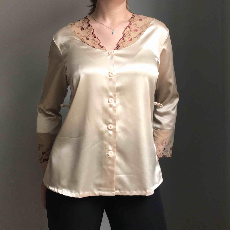 Så fin blank pyjamasskjorta i ljust guld med knappar framtill och spets i beige med mörkrött mönster vid krage och ärmar • perfekt till både vardags och fest • ingen storlek men sitter som en M • i bra skick!. Blusar.